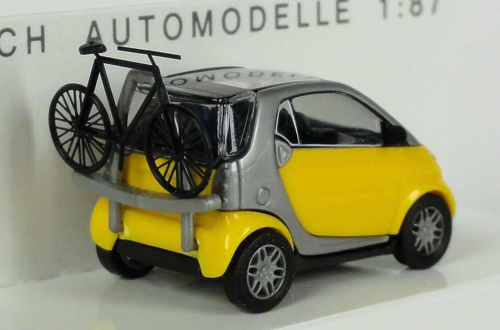 Foto 1:87 MCC Smart City-Coupé gelb/silber mit Fahrradträger und Fahrrad Busch 48907